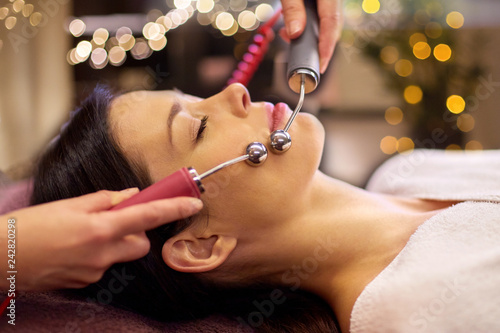 Leinwanddruck Bild people, beauty, cosmetology and technology concept - beautiful young woman having needle free mesotherapy or hydradermie facial treatment by microcurrent firming device in spa