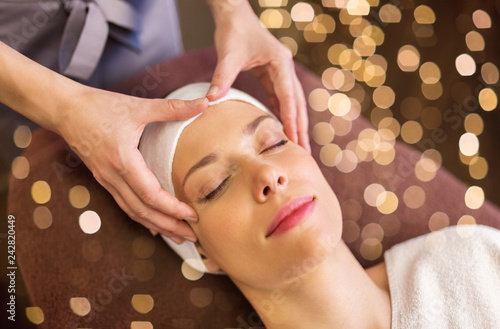 Leinwanddruck Bild people, beauty, lifestyle and relaxation concept - beautiful young woman lying with closed eyes and having face and head massage at spa