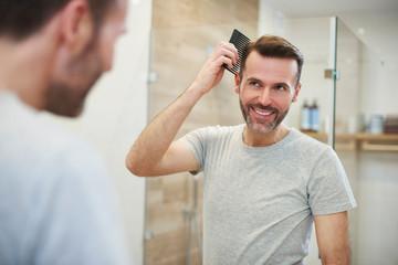Man combing his hair in the bathroom © gpointstudio