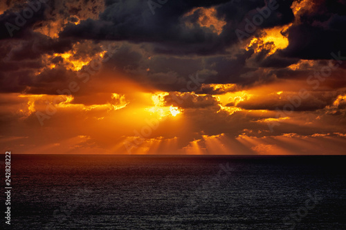 Foto Murales Dramatic sunset in the sea behind the dark heavy clouds