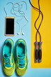Pair of sport shoes, skipping rope and cellphone with earphones. New sneakers on blue and yellow pastel background, copy space. Overhead shot of running foot wear. Top view, flat lay