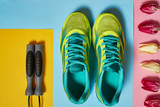 Pair of sport shoes, skipping rope and tulips on colorful pastel background. New sneakers on pink, blue and yellow paper, copy space. Overhead shot of running foot wear. Top view, flat lay