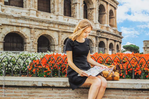 girl sitting with map on background of the Colosseum