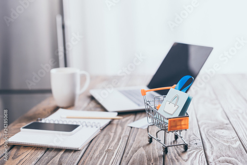 selective focus of toy shopping bag in small shopping trolley with laptop on background