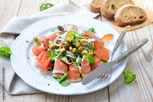Leinwandbild Motiv Blattsalat mit Südtiroler Speck, serviert mit Parmesan und Croutons – Green salad with South Tyrolean bacon, served with rye bread
