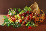 Fruits and flowers on the table with a brown tablecloth. Grapes, peaches, apples and rose flowers
