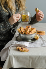 Italian dry cookies cantucci or biscotti with almond nuts stacked on a old plate on a table.