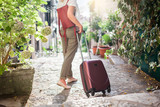 Fototapeta Na drzwi - Girl traveler with suitcase is on stone stairs. Young woman tourist is searching hotel at italian town streets with green plants. Concept of travel, vacation, female tourism, adventure, trip. © Marina Andrejchenko