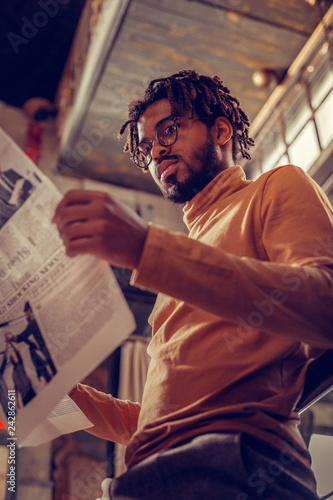 Concentrated young male person reading business news