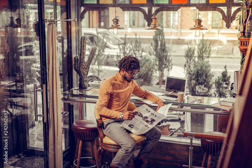 Attentive brunette international freelancer having coffee break