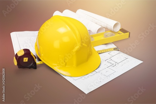 Foto Murales Yellow hard hat and blueprints on wooden desk in a construction