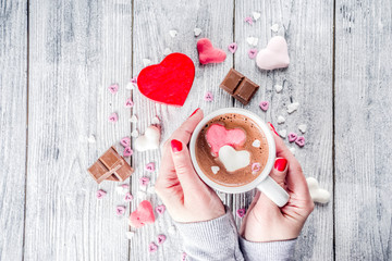 Girl hands hold hot chocolate with marshmallow hearts