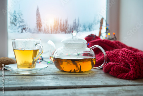 Cup of coffee or tea, smartphone and earbuds with autumn leaves near a window. Autumn playlist concept. Autumn music for rainy days. - 242871467