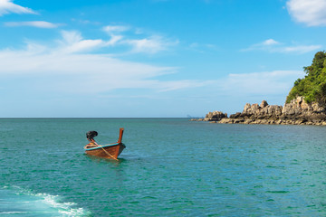 traditional Thai boat is anchored near a small rocky island in a calm sea on a sunny day