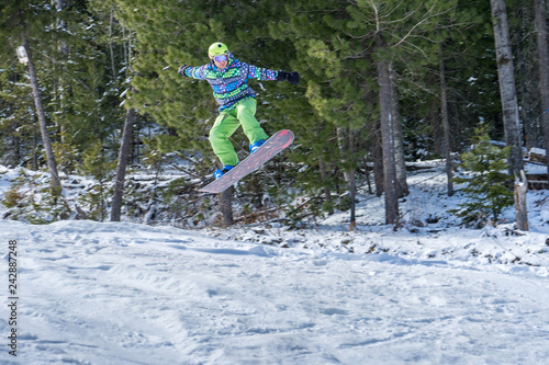 obraz PCV Snowboarder jumping in the mountains on a forest background