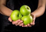 Green apples in woman hands on black background - 242889608