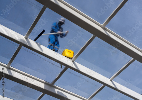 Male worker washing large expanse of glass roof over swimming pool