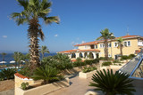View of the yellow building, the blue sea and green palm trees in the hotel, Greece.. - 242901231