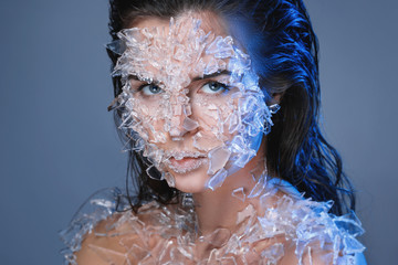 Female face covered with a lot small pieces of glass or ice © blackday