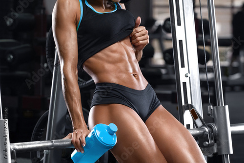 Fitness woman showing abs and flat belly. Muscular girl, shaped abdominal - 242917048