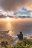 Young man sitting on the edge at the top of Lion's head mountain in Cape Town with a beautiful sunset view - 242947018