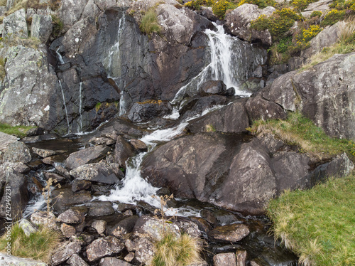 Aerial drone view landscape of river flowing down waterfall and over rocks in Snowdonia