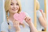 Blonde woman in braids holding heart - 242954687