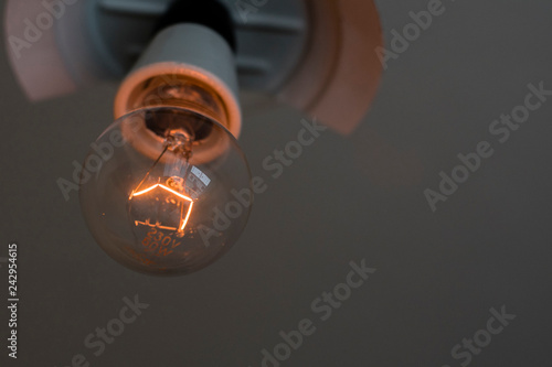 Foto Murales Fired filament in bulb on ceiling light.