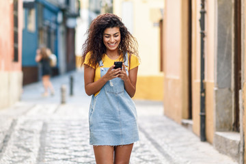North African woman walking on the street looking at her smart phone © javiindy