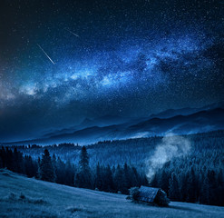 Milky way over cottage in Tatra mountains at night, Poland