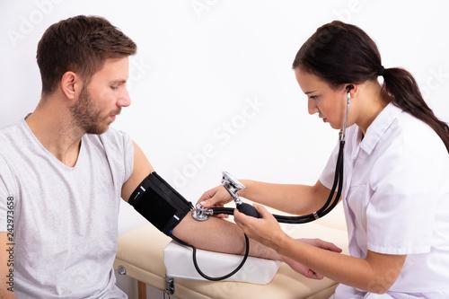 Leinwanddruck Bild Doctor Checking Blood Pressure Of Patient