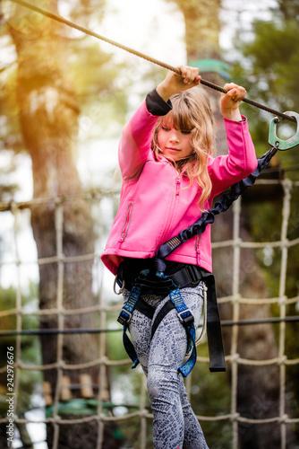 belle jeune fille dans un parc d'accrobramche - 242976676