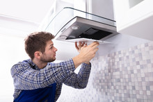 "Постер, картина, фотообои ""Young Male Fixing Kitchen Extractor Filter"""