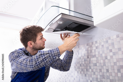Young Male Fixing Kitchen Extractor Filter