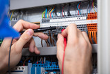 Fototapeta Panele - Male Electrician Examining Fuse Box With Multimeter © Andrey Popov
