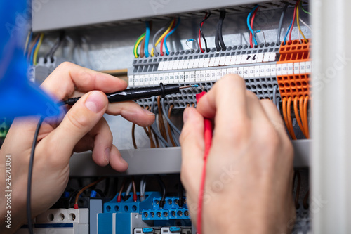Male Electrician Examining Fuse Box With Multimeter - 242988051