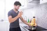 Young Man Looking At Burning Cooking Pot - 242988272