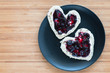 Heart shaped toasts on a plate over wooden background, top view