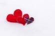 Three textile hearts on snow, love concept