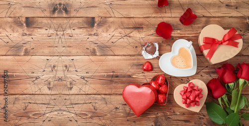 Valentine's day banner with coffee cup, heart shape chocolate, rose flowers and gift boxes on wooden background.