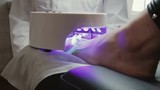 Nails on the client's foot are dried under the lamp after applying the gel Polish. Hardware pedicure in the beauty salon. Concept of beauty - 242998073