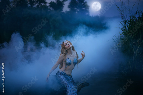 Leinwandbild Motiv Neptune's daughter absorbs and eats moonlight, the magnificent sea ruler sits on a stone in the night river and rests in a thick fog, a fabulous character with art processing photos