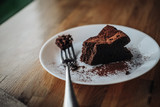 One slice of vegan chocolate brownie cake on wooden table. Sugar free, wheat free, dairy free, flourless dessert. Dark mood food photo. Healthy eating, lifestyle concept. Copy space - 243006269