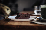 One slice of vegan chocolate brownie cake on wooden table. Sugar free, wheat free, dairy free, flourless dessert. Dark mood food photo. Healthy eating, lifestyle concept. Copy space - 243006442