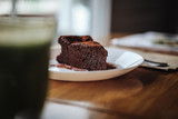 One slice of vegan chocolate brownie cake on wooden table. Sugar free, wheat free, dairy free, flourless dessert. Dark mood food photo. Healthy eating, lifestyle concept. Copy space - 243006844