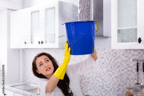 Woman Collecting Water Leaking From Ceiling In Bucket