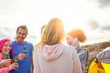 Happy friends drinking beers and having fun camping with tent outdoor - Group of young people enjoying and laughing together in vacation - Travel and youth holidays lifestyle concept - 243022276