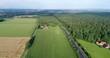 Landstraße mit Feldern und Wald aus der Luft, Deutschland
