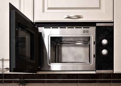 Open empty microwave in the kitchen cupboard