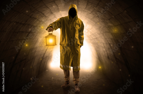 Ugly man in raincoat walking with glowing lantern in a dark tunnel